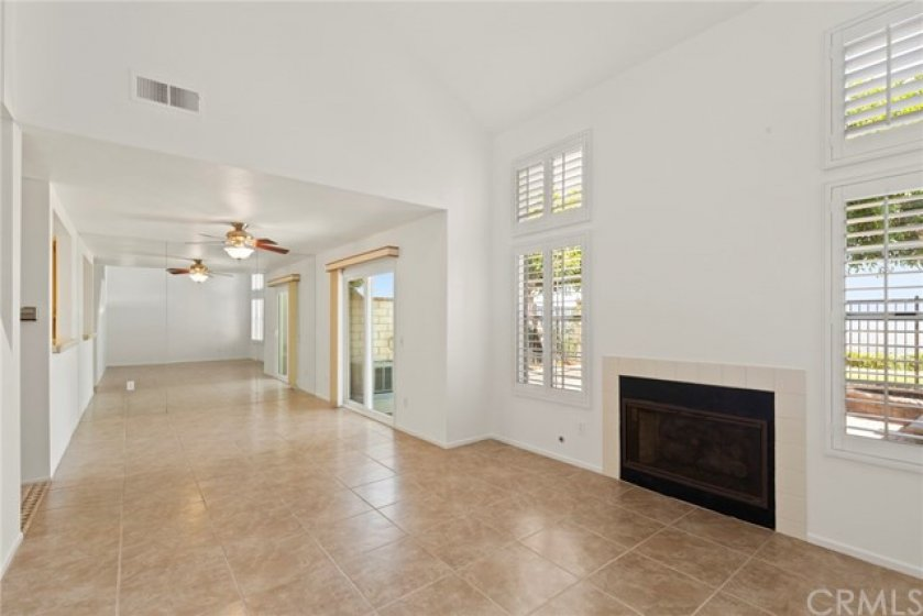 Living Room with Cathedral Ceilings, Tile Floors, Gas Fireplace, Plantation Shutters, and Views.