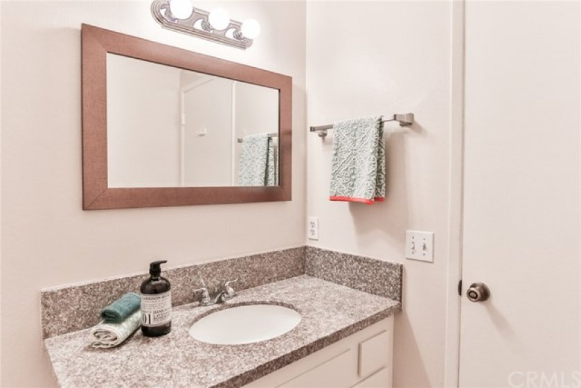 Downstairs half bath with upgraded countertops.