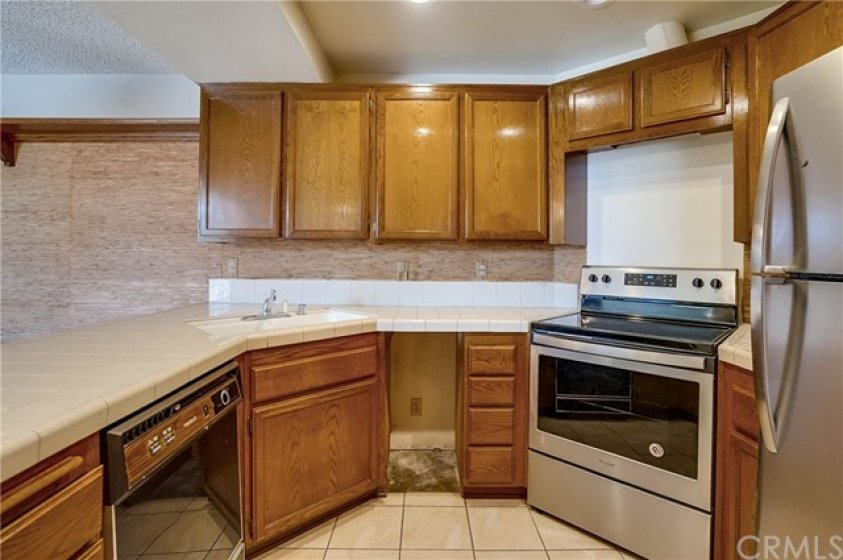Kitchen with newer stove/oven and refrigerator, and space for under counter trash receptacle.