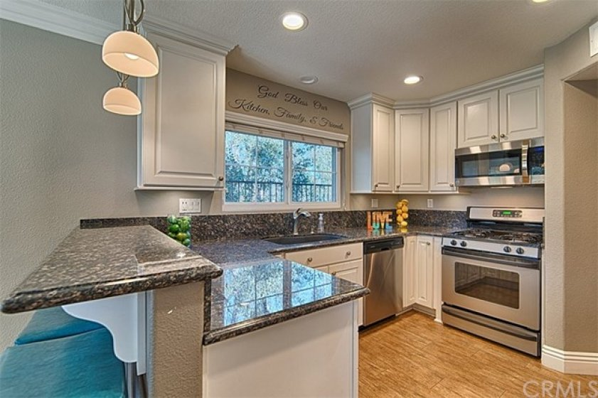 Stainless steel appliances, recessed lighting, wood tile flooring round out this beautiful kitchen.