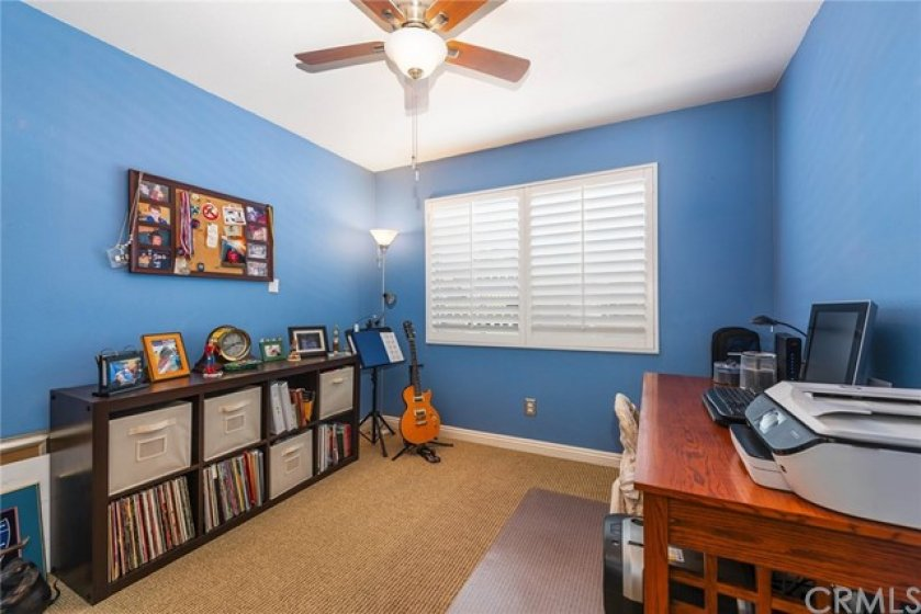 Sunny secondary bedrooms offer plantation shutters, upgraded baseboards, newer upgraded ceiling fans, and neutral carpeting.