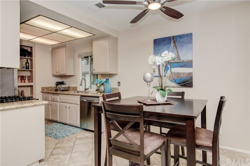 SPACIOUS DINING AREA WITH TILE FLOORING AND CEILING FAN.