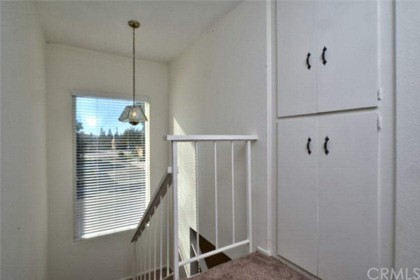 There's plenty of linen storage at the top of the stairs, and the large window lets in abundant natural light.