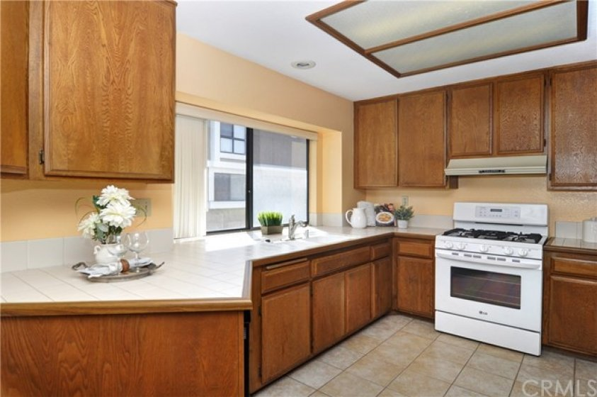 Sunny and roomy kitchen with tile flooring, dishwasher, gas stove and plenty of counter and cabinet space