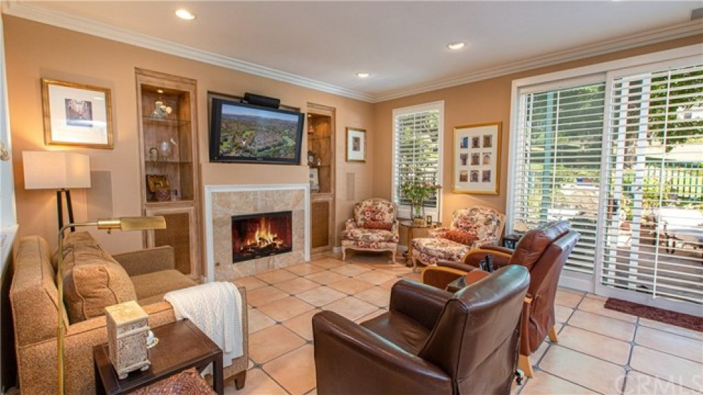 Cozy family room features shutters, custom tile flooring and fireplace surrounded by lighted built-in display cases.