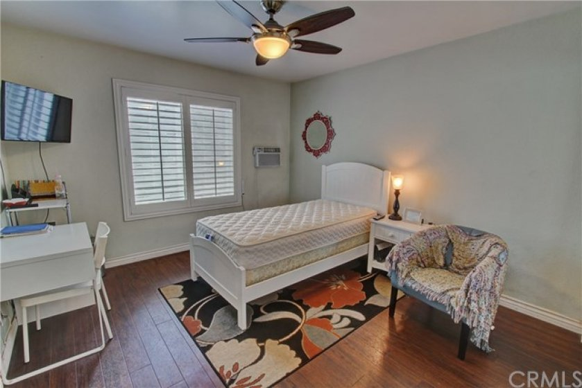 Large second bedroom features plantation shutters, hardwood flooring,television (3 in total) and wall ac (4 in total).