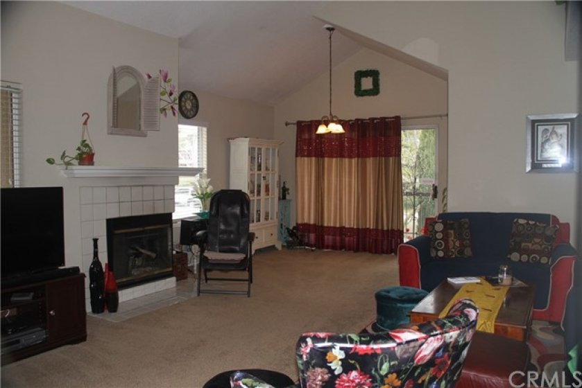 Great room features vaulted ceiling, fireplace and dining area with direct access to covered patio.