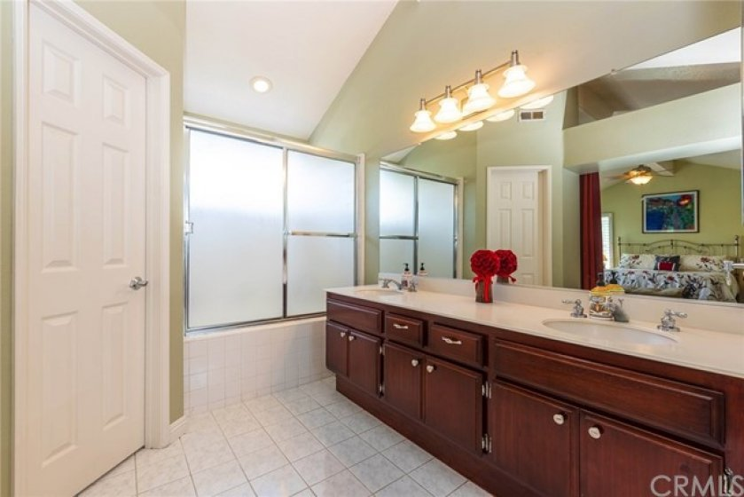 Master bath features rich wood cabinetry, upgraded lighting, dual sinks, tile flooring, soaking tub, and walk-in closet.
