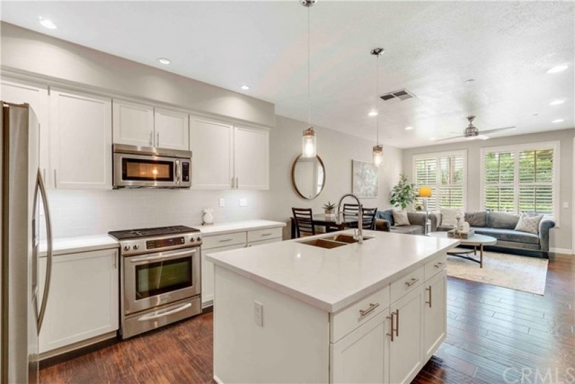 The stunning remodeled kitchen hosts a center island with breakfast counter, white shaker cabinetry, white quartz countertops, subway tile backsplash, and Kitchen Aid stainless steel appliances.