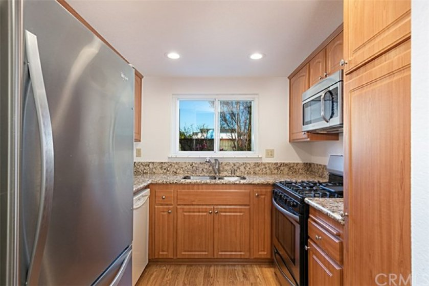 Your new Kitchen, with newer cabinets with self closing drawers, granite counter tops, dishwasher, newer stainless steel range, and stainless steel refrigerator, all under new LED lights.