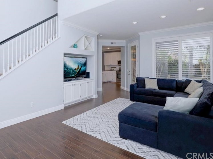 A soaring ceiling when you enter leads to the large living area with recessed lighting, crown molding, high baseboards, and wood laminate floors opens to the kitchen and the backyard.