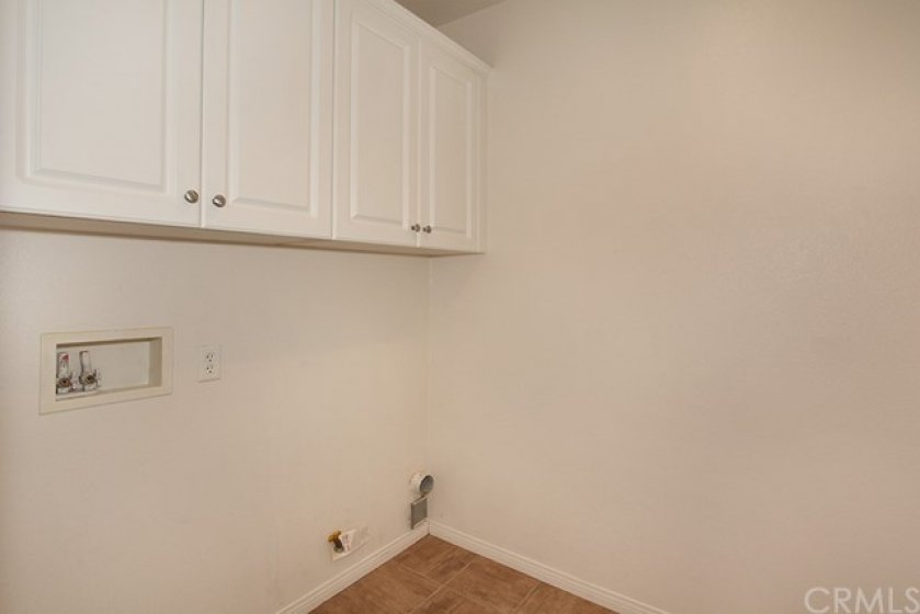 Inside laundry room with cabinets.