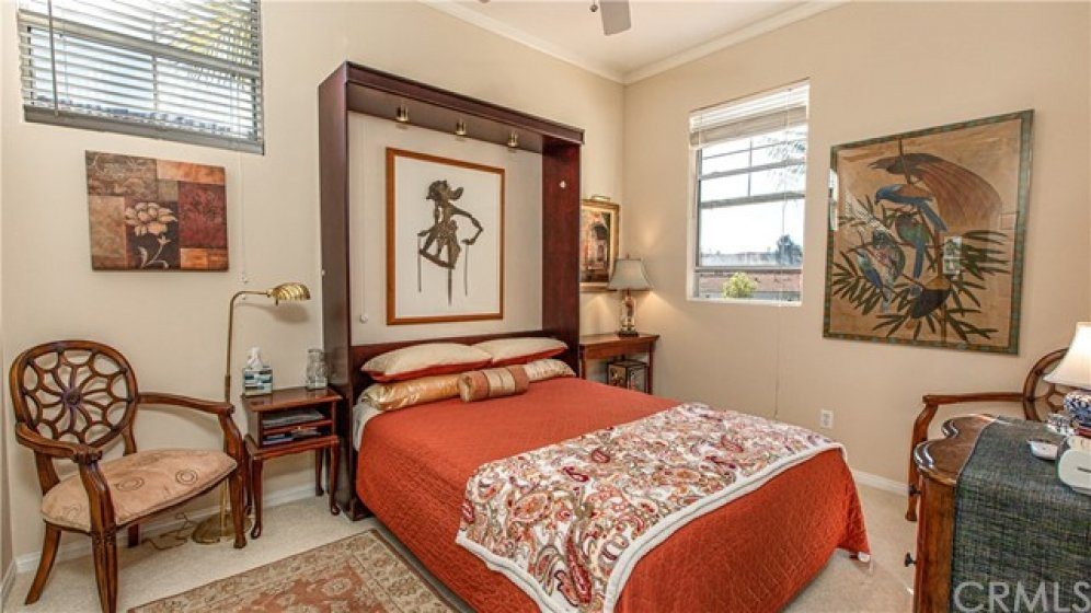 Guest bedroom with high ceiling, plenty of natural light and beautiful Murphy bed with lighting and ceiling fan.