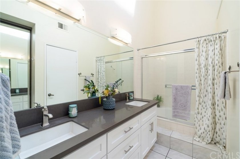 En suite master bath includes upgraded quartz counters and dual sinks
