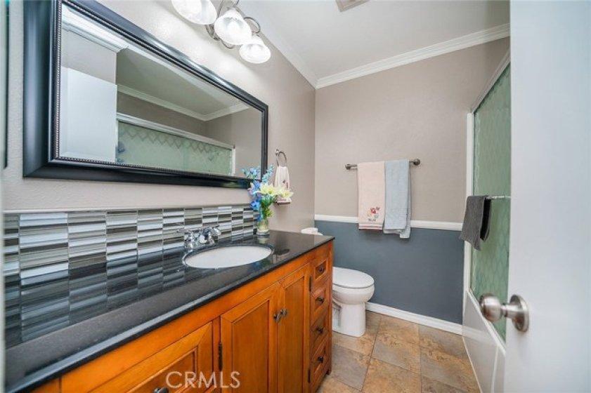 Full bathroom with granite counter top, back splash and glass door.