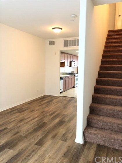 Kitchen, living room and carpeted stairs going up to 2 bedrooms and 2 bathrooms.