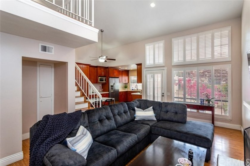 Living room with shutters and view of patio, kitchen and dining area.