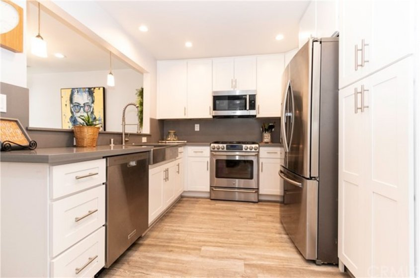 Crisp white kitchen with quartz counters and stainless steel appliances.