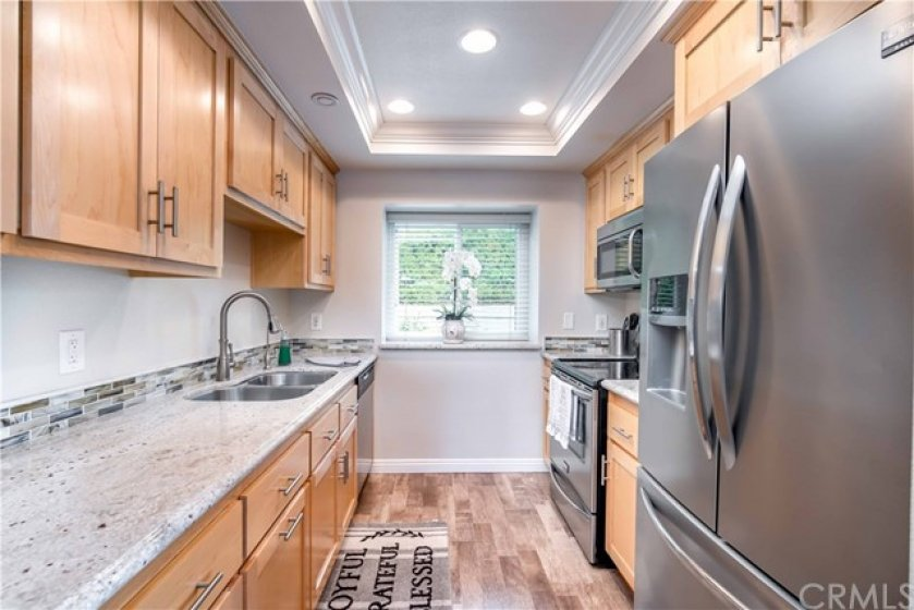 Updated kitchen with granite counter tops, custom backsplash, and stainless steel appliances