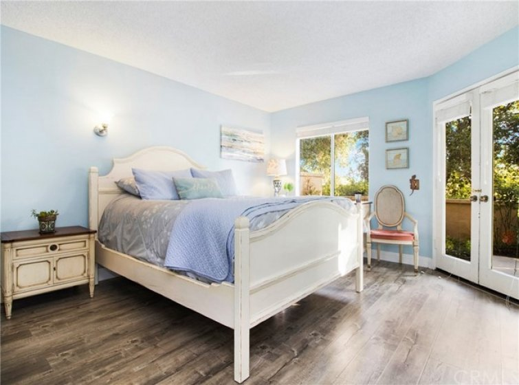 Relaxing master bedroom with double door entry to the patio