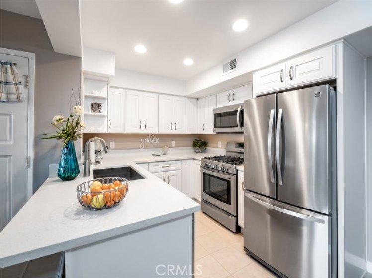 kitchen has quartz counters & stainless steel appliances