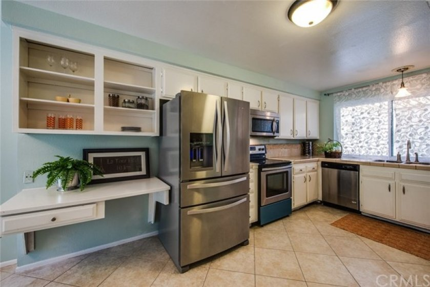 This open kitchen with white cabinetry has plenty of room for you to create your culinary masterpieces!  Newer stainless steel appliances too!