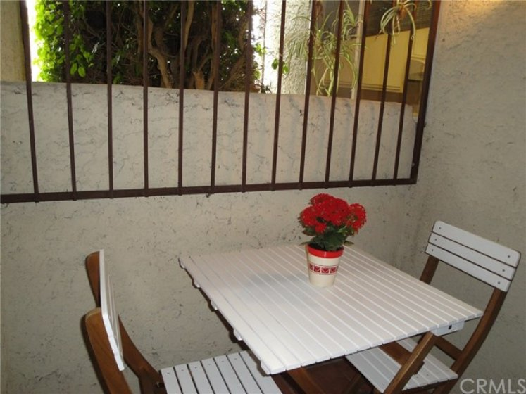 Covered breezeway, large enough for a little table and chairs. It is covered and leads to the garage, you will not get wet when it rains.