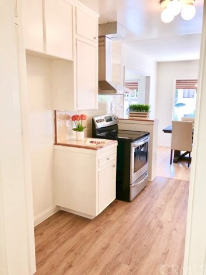 The kitchen flooring is a slight shade darker than the original hardwood flooring, and is better equip to handle spills, etc.