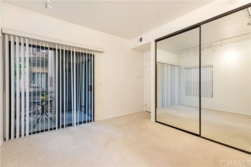 Guest bedroom with mirrored closet and access to enclosed front patio