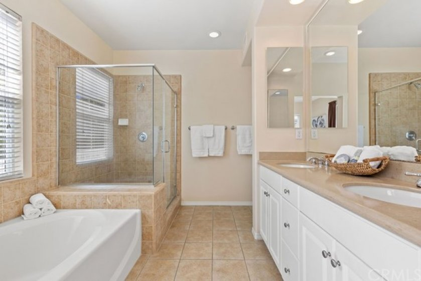 A large soaker tub and oversized shower with clear glass doors provide a spa like experience in the primary bedroom en-suite bathroom.