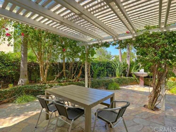 Extra large backyard with flagstone hardscape, covered pergola, and a variety of lush trees and plants.