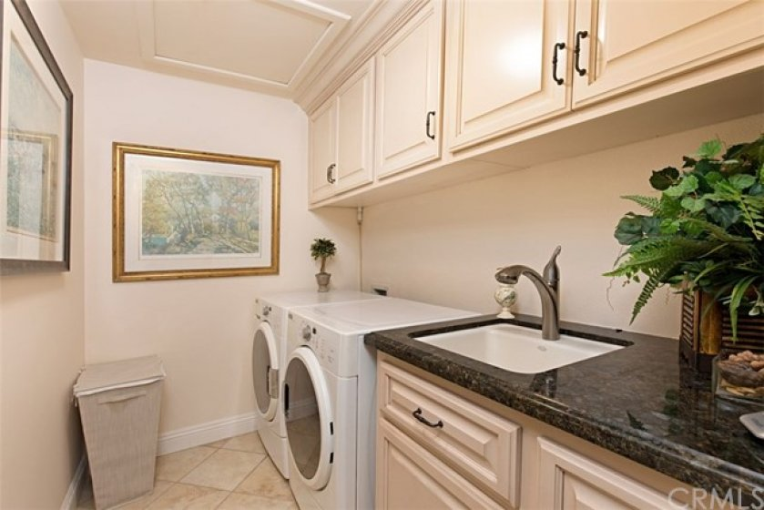 Indoor Laundry Room with custom cabinetry, sink and granite countertops.