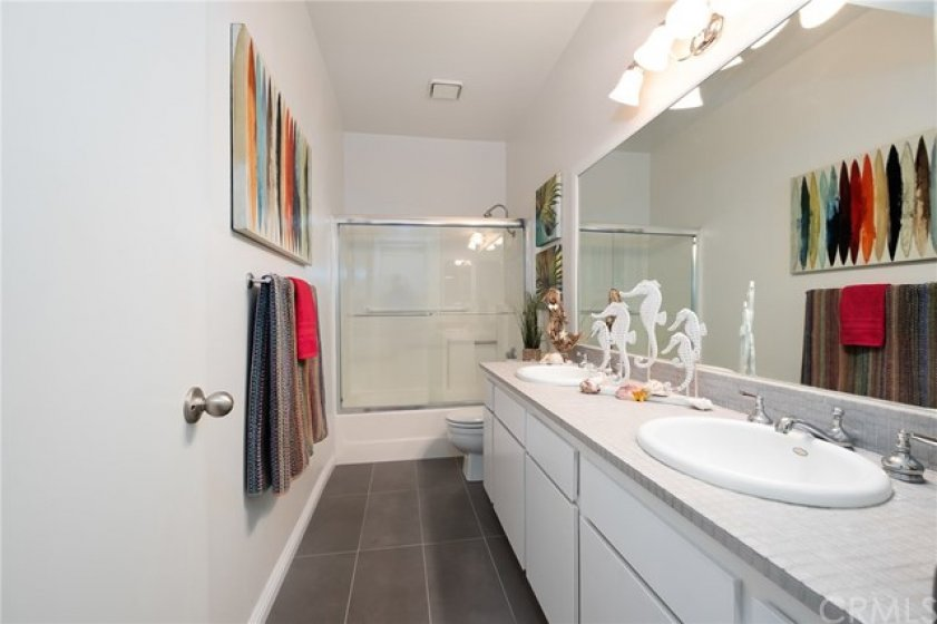 Bathroom has attractive gray flooring and countertop plus shower and tub combo with door