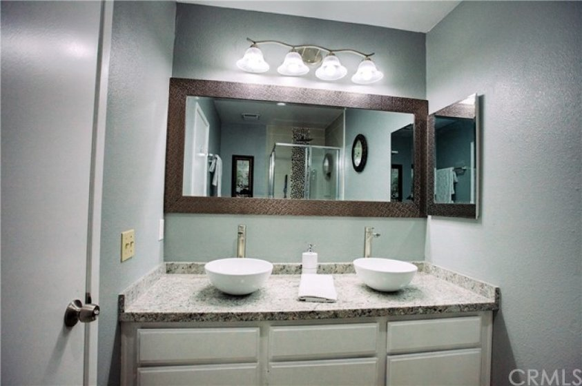 Beautifully upgraded master bathroom 1 with Formica counters that look like granite.  Dual bowl sinks with new hardware, new light fixture, new custom mirror and new medicine cabinet. Freshly painted, new tile floor.