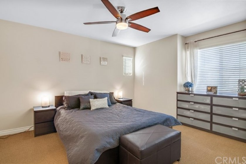 Spacious master bedroom with large window and ceiling fan.