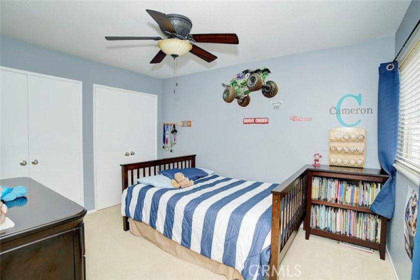 2nd bedroom has 2 side by side closets, ceiling fan, scraped ceilings