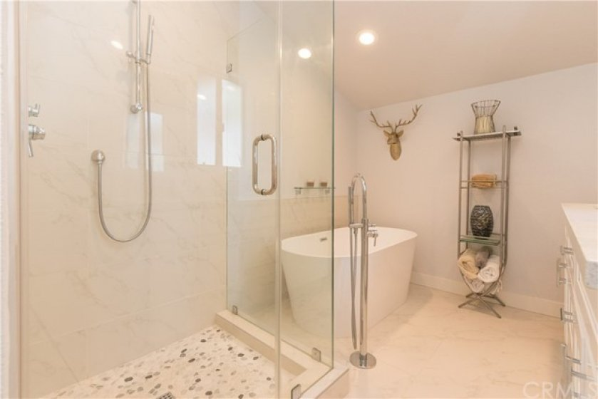 Glass enclosed shower and freestanding tub.