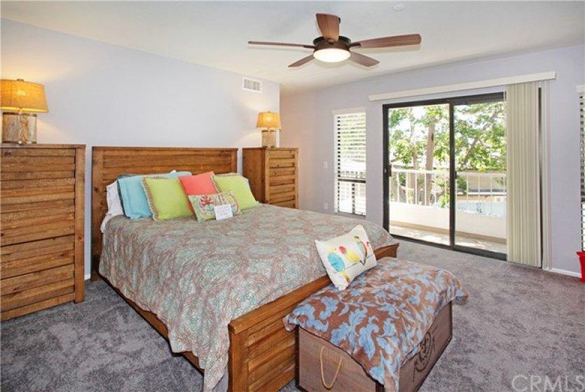 Spacious master bedroom with en suite bathroom, and sliding door to private balcony overlooking greenbelt