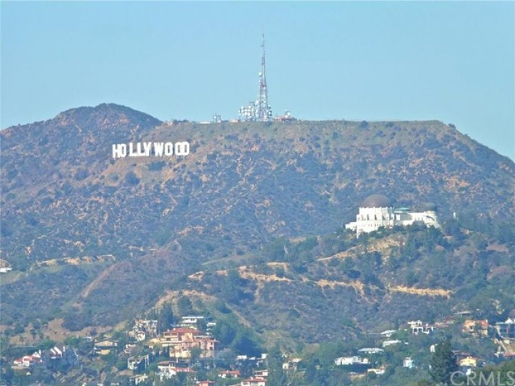 rooftop view, zoomed in, of the Hollywood Sign and Griffith Observatory