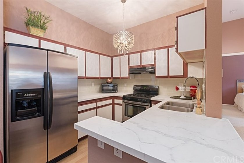 Nice and bright kitchen with stainless steel gas range and hood, quartz counters and stainless steel sink and updated faucet.