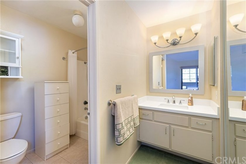 Bathroom and dressing area with beautiful Quartz vanity, new mirror, and light fixture.