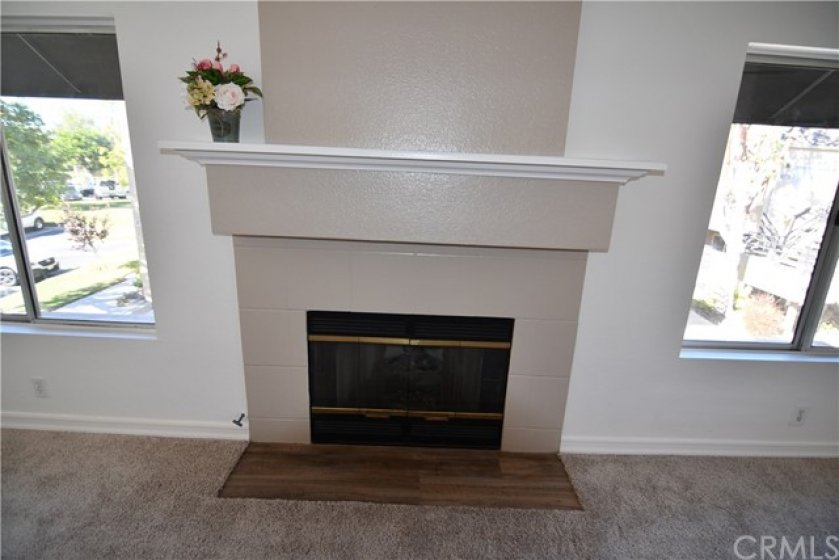 Close up of your new fireplace and upgraded wood mantle. Hearth is upgraded with laminate flooring also. See the view of the greenbelt out to the left.