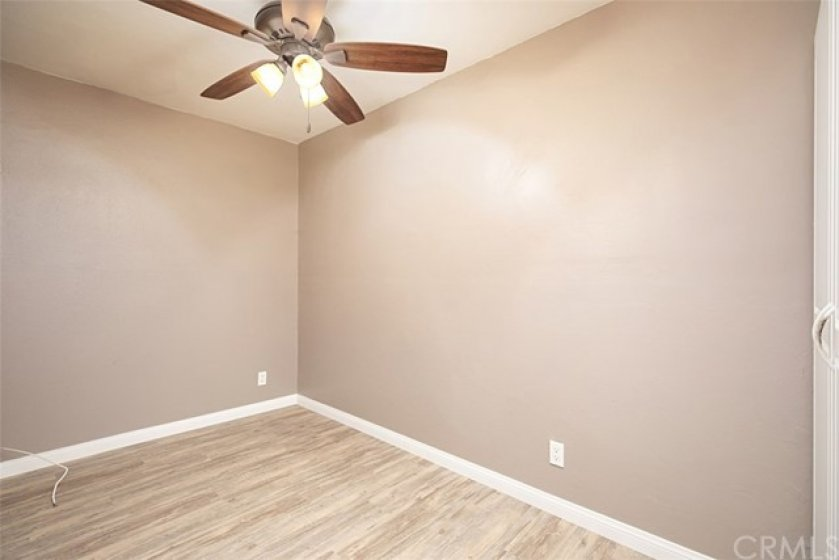 Smaller room may be used as an office, exercise or resting room and features ceiling fan, smooth ceilings, new luxury vinyl plank flooring, wide baseboards