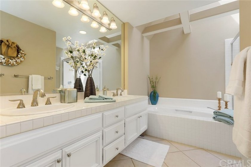 Master bathroom with dual vanity, tub, stall shower and skylight