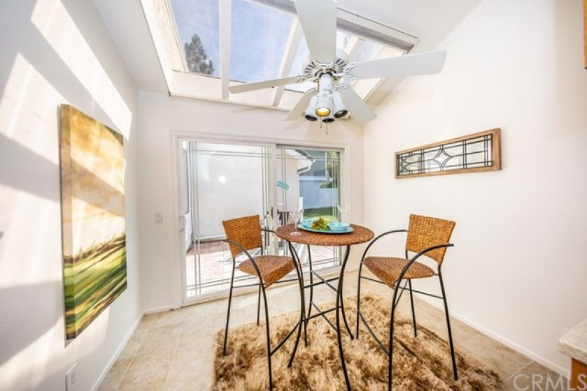 Breakfast nook with skylight, ceiling fan, and a sliding door out to the atrium.