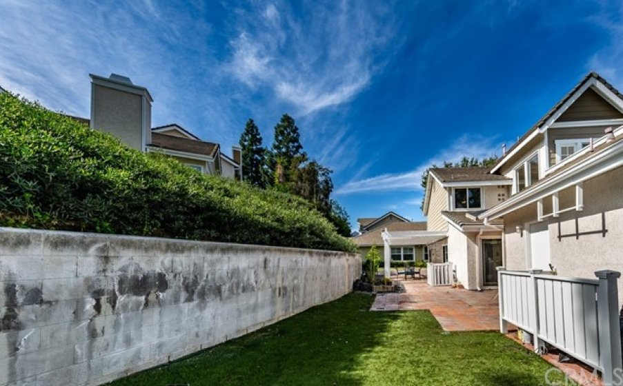 Large backyard with artificial grass and private block wall.