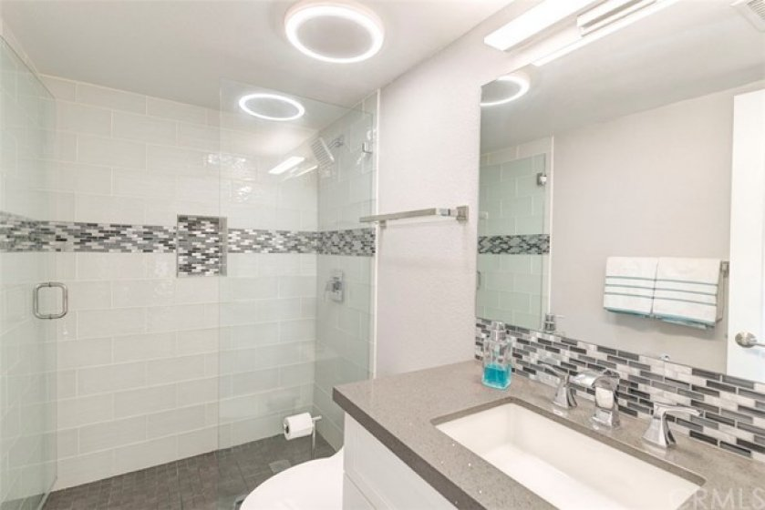 Beautifully remolded Master Bathroom with quartz counters, walk in shower with glass tiles and new modern shower doors.