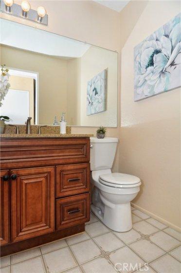 Downstairs half bath has upgraded vanity with quartz countertop