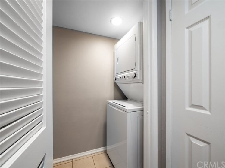In hall is entry to laundry room with stackable washer and dryer for you