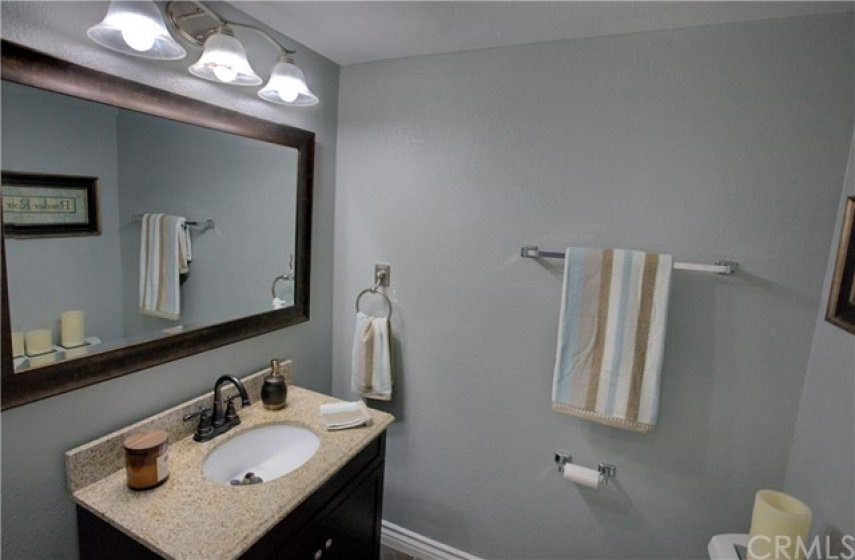 Remodeled powder room downstairs with new vanity, new mirror, new light fixture, freshly painted, new tile floor.